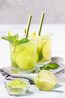 Due bicchieri di tè freddo verde matcha con lime, ghiaccio, menta, cannucce di bambù su grigio chiaro.