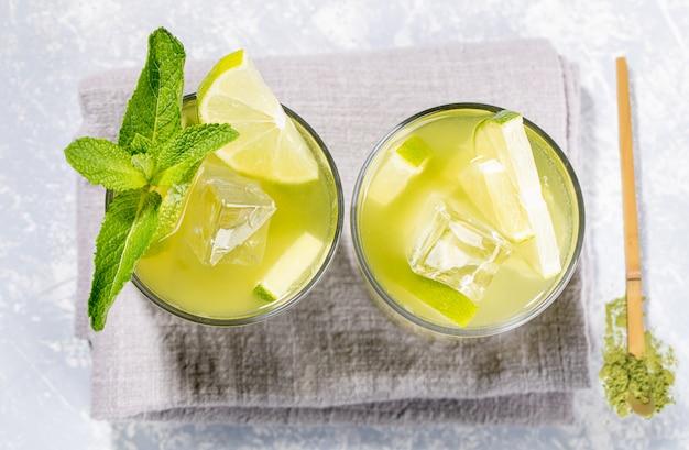 Due bicchieri di tè verde freddo matcha con lime, ghiaccio, menta e cucchiaio di legno di polvere su grigio. vista dall'alto.