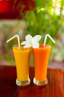 Due bicchieri di vetro con succo appena spremuto e fiori di frangipane