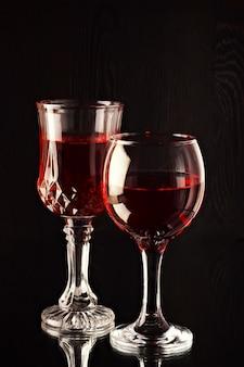 Due bicchieri di vetro con vino su uno sfondo scuro.