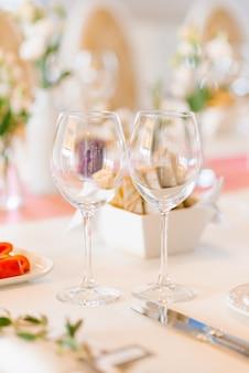 Due bicchieri di vetro vuoti nella decorazione di nozze su un tavolo del banchetto festivo