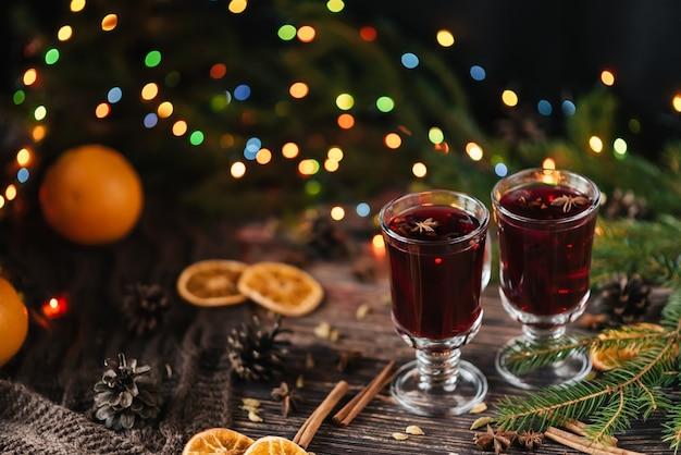 Due bicchieri di vin brulé caldo su un tavolo di legno decorato di natale
