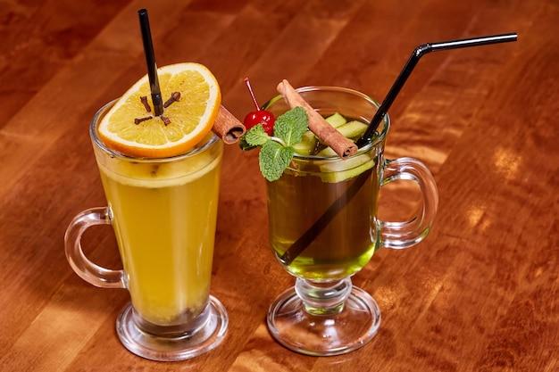 Due bicchieri di vin brulè con bastoncini di arancia e cannella