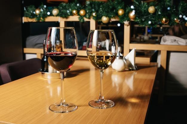 Due bicchieri di vino bianchi e rossi che stanno su una tavola con la luce della candela al sole