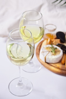 Due bicchieri di vino bianco e piastra con formaggi assortiti, frutta e altri snack per la festa