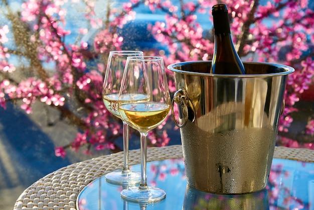 Due bicchieri di vino bianco freddo su un tavolo di vetro sullo sfondo del mare e fiori.