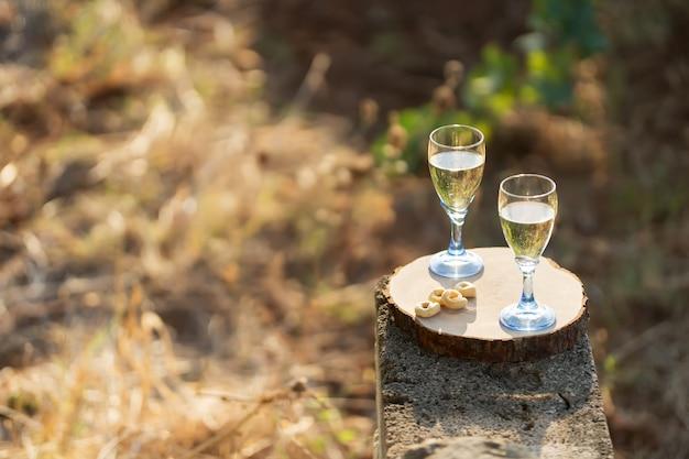 Due bicchieri di vino bianco fresco su una tavola di legno