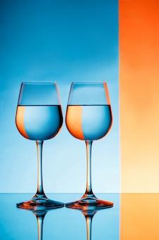 Due bicchieri di vino con acqua su sfondo blu e arancione.