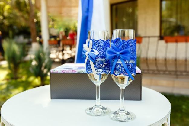 Due bicchieri di vino con nastro blu e confezione regalo su un tavolo sulla cerimonia di nozze
