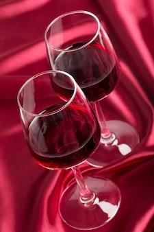 Due bicchieri di vino con vino rosso sulla seta rossa