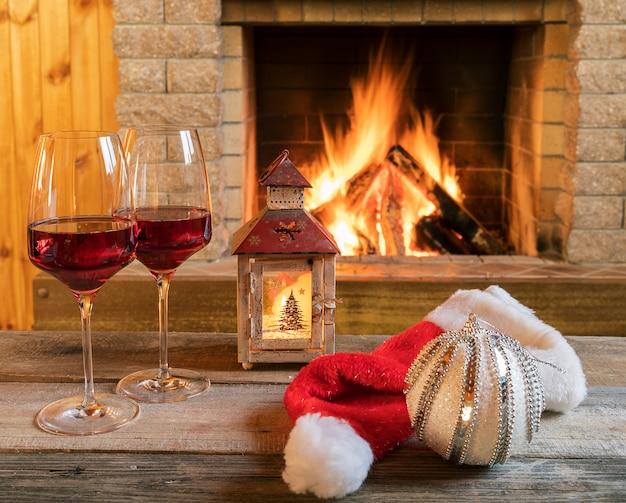 Due bicchieri di vino e lanterne di natale vicino al camino accogliente in casa di campagna.
