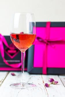 Due bicchieri di vino rosato sul tavolo di legno bianco con scatole regalo rosa