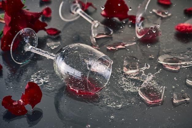 Due bicchieri di vino rosso, caduti e rotti, giacciono su un tavolo di vetro con frammenti di vetro e petali di rose rosse fresche