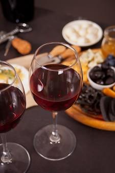 Due bicchieri di vino rosso e piastra con formaggi assortiti, frutta e altri snack per la festa