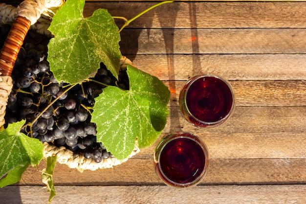Due bicchieri di vino rosso e un cesto di uva