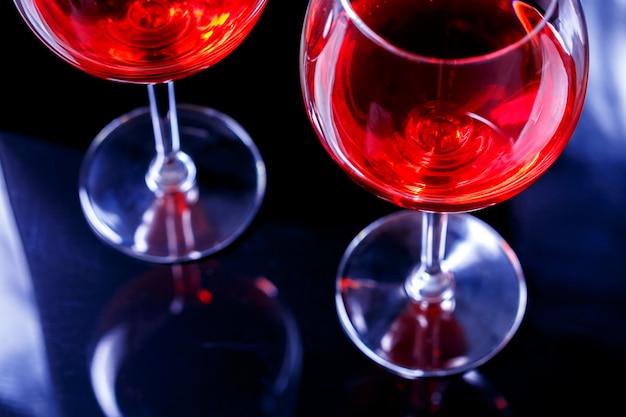 Due bicchieri di vino rosso in discoteca con la riflessione. bevi il concetto di relax.