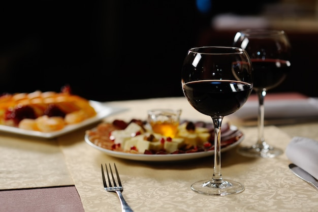 Due bicchieri di vino rosso sullo sfondo dei piatti