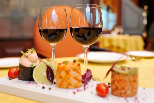 Due bicchieri di vino rosso sullo sfondo delle delizie nel ristorante