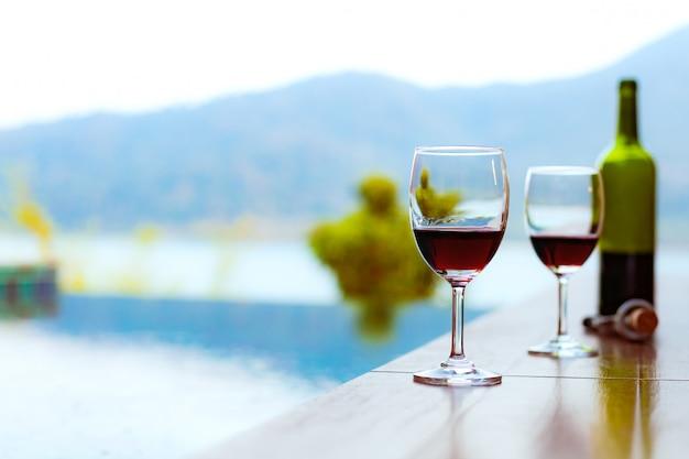 Due bicchieri di vino rosso vicino alla piscina con una vista spettacolare sul mare