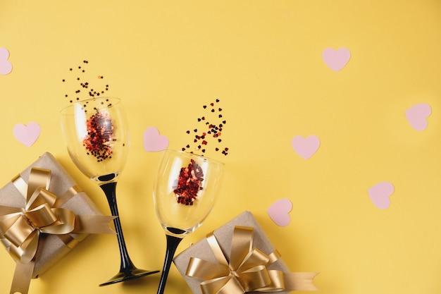 Due bicchieri di vino tintinnanti, varie scatole regalo