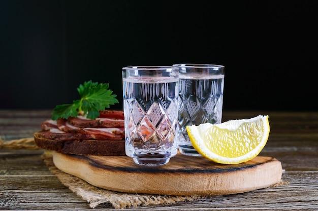 Due bicchieri di vodka con fetta di limone e pane di segale con pancetta salata sullo sfondo scuro.
