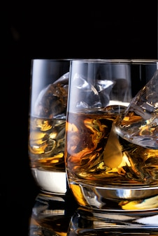 Due bicchieri di whisky sul tavolo con una bottiglia