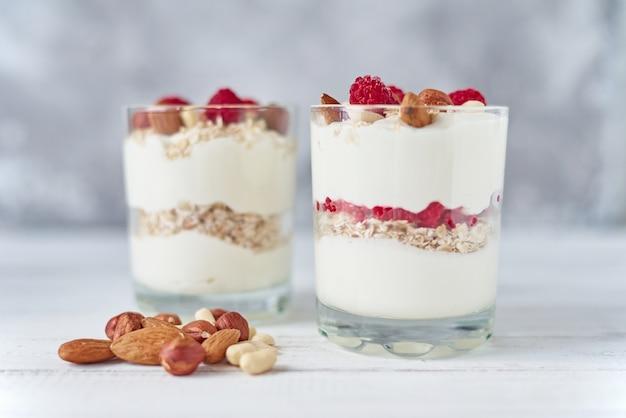Due bicchieri di yogurt greco granola con lamponi, fiocchi d'avena e noci su uno sfondo bianco. alimentazione sana