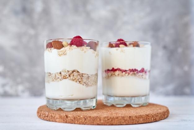Due bicchieri di yogurt greco muesli con lamponi, fiocchi d'avena e noci. alimentazione sana