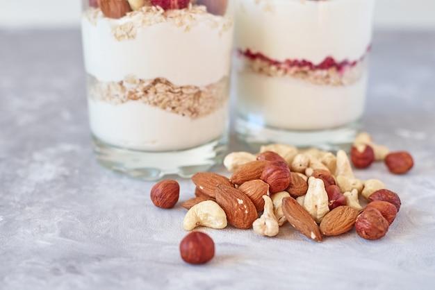 Due bicchieri di yogurt greco muesli con lamponi, fiocchi d'avena e noci