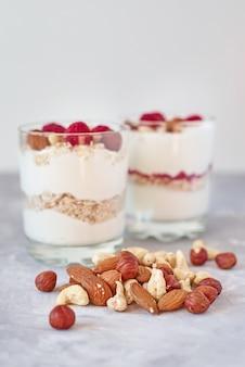 Due bicchieri di yogurt greco muesli con lamponi