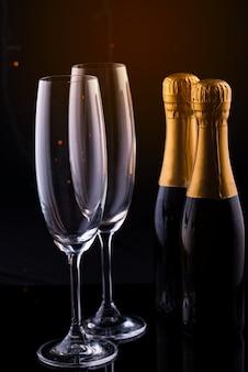 Due bicchieri e bottiglie di champagne