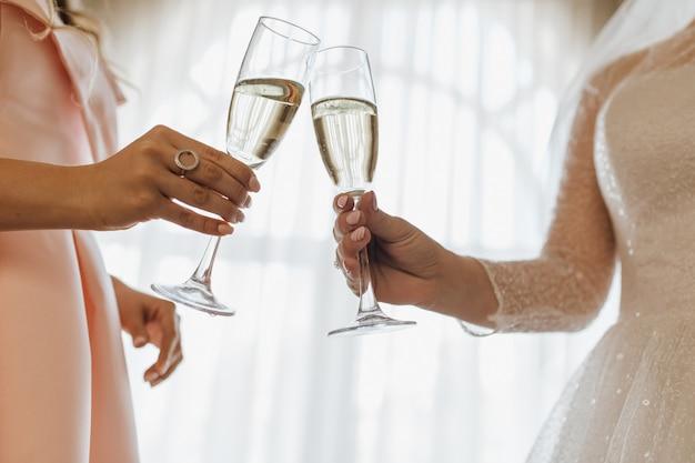 Due bicchieri pieni di champagne nelle mani della sposa e della damigella d'onore