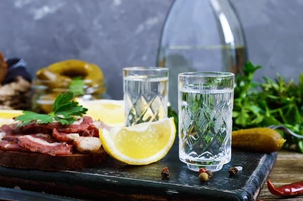 Due bicchierini di vodka con fetta di limone, cetrioli sottaceto e pane di segale con pancetta salata sullo sfondo scuro.