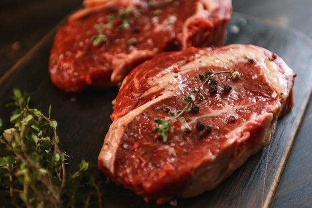 Due bistecche di manzo marmorizzate crude in olio d'oliva e spezie pronte per la frittura.