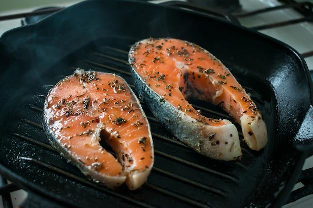 Due bistecche di salmone crudo con spezie ed erbe aromatiche su una bistecchiera