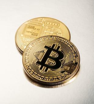 Due bitcoin d'oro su uno sfondo grigio chiaro
