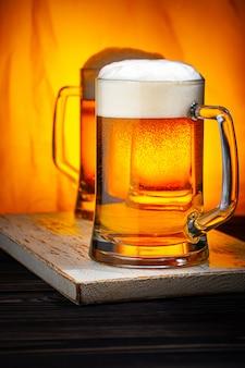 Due boccali di birra leggera con schiuma bianca