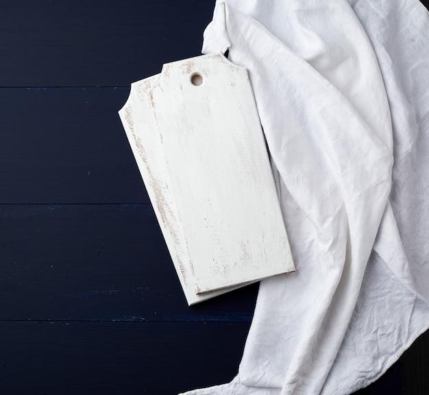 Due bordi da cucina bianchi rettangolari di taglio su un blu di legno, accanto ad un asciugamano bianco del tessuto, vista superiore