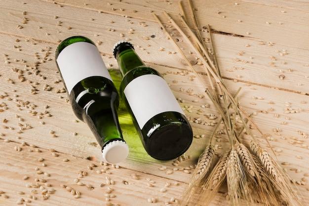 Due bottiglie alcoliche e spighe di grano su superficie in legno