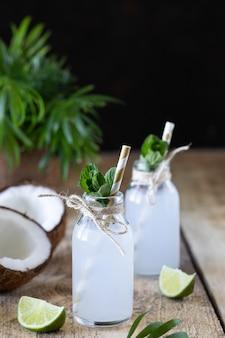 Due bottiglie di acqua di cocco su un tavolo di legno.