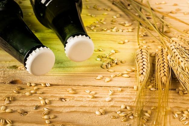 Due bottiglie di birra e spighe di grano sul contesto in legno