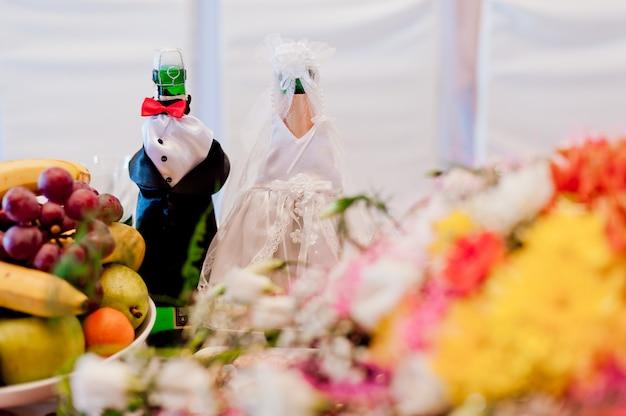 Due bottiglie di champagne che indossa come una sposa e lo sposo in piedi sul tavolo di nozze.