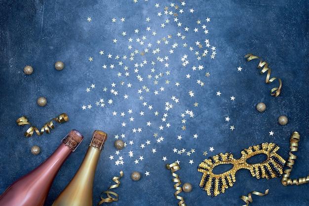 Due bottiglie di champagne colorate con maschera di carnevale, stelle di coriandoli e stelle filanti di partito sul blu.