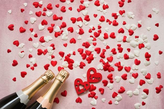 Due bottiglie di champagne con cuori rossi e bianchi su sfondo rosa