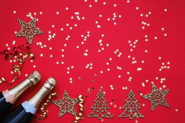 Due bottiglie di champagne con maschera di carnevale, stelle di coriandoli e stelle filanti di partito sul rosso.