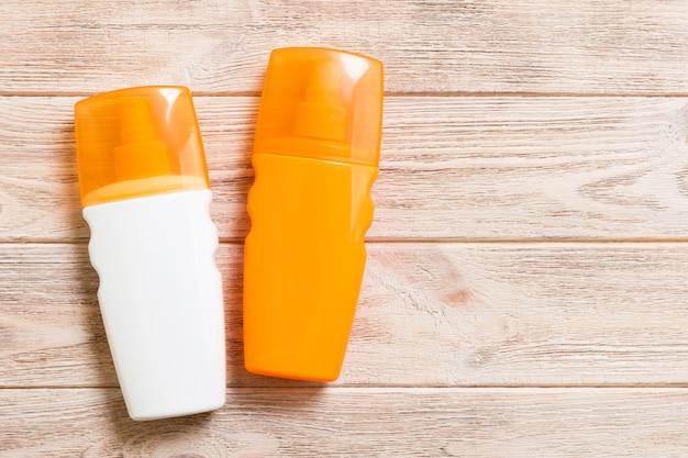 Due bottiglie di crema solare su un tavolo di legno luminoso, vista dall'alto con spazio di copia