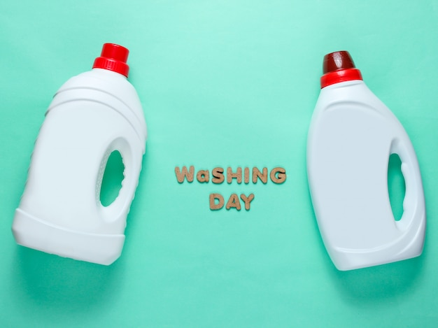 Due bottiglie di gel detergente sulla superficie blu con il giorno di lavaggio del testo