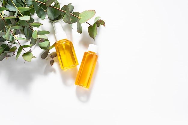Due bottiglie di oli essenziali biologici e ramoscelli di eucalipto freschi su sfondo bianco.