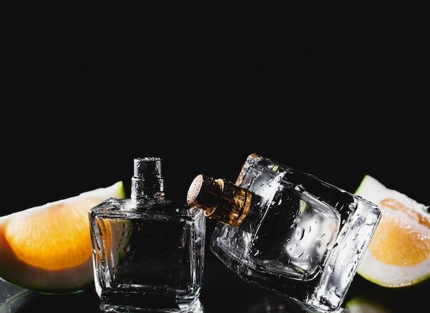 Due bottiglie di profumi con agrumi sul nero