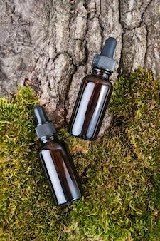 Due bottiglie di vetro marroni e pipetta con siero di siero, olio essenziale su muschio verde e sfondo di corteccia di albero.